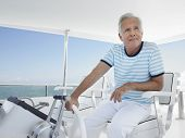 Happy middle aged man sitting at helm of luxury yacht