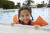 Portrait of little girl wearing water wings relaxing on edge of swimming pool