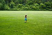 Small child running through field towards woods