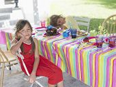 Portrait of a girl with boy sleeping at outdoor table after birthday party