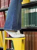 image of shelving unit  - Closeup lowsection of a young man standing on stool reaching for book in library - JPG