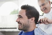 stock photo of barbershop  - Closeup of happy man getting an haircut from barber in hair salon - JPG