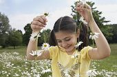 Smiling young girl holding daisy chains in meadow