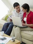 Pareja joven sentado en el sofá con portátil y facturas