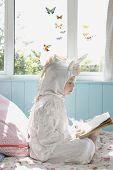 Side view of a young girl reading book in unicorn costume on bed