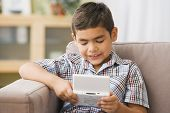 Boy playing handheld video game on sofa