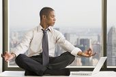 Mixed race businessman practicing yoga at desk
