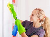 Woman cleaning cupboard. Female doing housework.