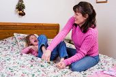 foto of tickle  - A mother tickling her elementary daugher on a big bed - JPG