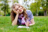 Hermosa soñadora adolescente tirado en el pasto en el parque con bolígrafo y cuaderno