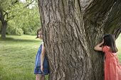 Two girls playing hide and seek by tree in park