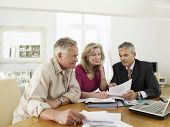 Mature couple sitting at table with financial advisor