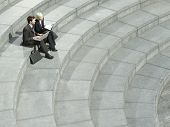 Elevated view of businessman and businesswoman using laptop on spiral stairs