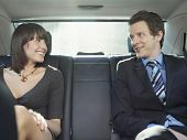 Happy young businessman and businesswoman talking in back seat of car