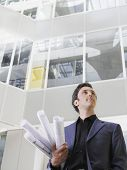 Low angle view of a businessman holding rolled blueprints under arm in atrium of office building