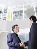 Low angle view of two businessmen shaking hands in office atrium