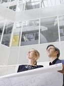 Low angle view of two smiling business people with blueprint in office atrium