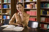 image of shelving unit  - Young woman with book sitting at desk in library - JPG