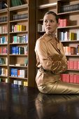 foto of shelving unit  - Thoughtful young woman sitting on desk in the library - JPG
