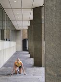 Full length of a female athlete crouching in starting position on pavement by pillars in portico