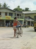 Rear view full length of a young woman on street walking with bicycle