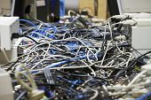 picture of cord  - Closeup of messed wires connecting computers and printers in office - JPG