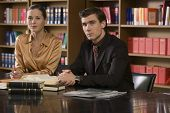 picture of shelving unit  - Portrait of a serious young man and woman sitting at desk in the library - JPG