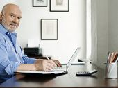 Side view portrait of a mature man using laptop and writing in notepad at home desk