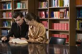 image of shelving unit  - Young man and woman studying at desk in the library - JPG