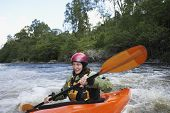 Smiling young woman kayaking in the river