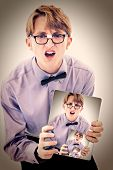 Adorable geeky teen boy holding electric notepad with photo of self.