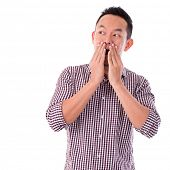Shocked Asian man covering his mouth by hand, isolated on white background. Asian male model.