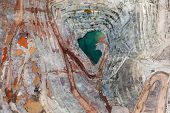 stock photo of open-pit mine  - Brillant colors explode in a vertical view of an open pit mining from above - JPG