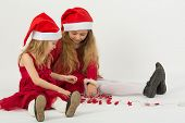 Two girls in a red dress in caps Santa Claus sitting on the floor and play with garland