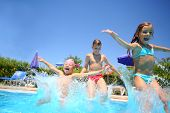 foto of yell  - Two little girls and boy fun jumping into the swimming pool - JPG