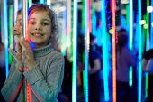 Little girl stands in mirror labyrinth illuminated with color lights