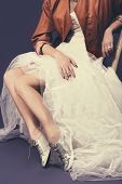portrait of untraditional bride with tulle wedding dress wearing sequin shoes and leather jacket sit