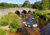 stock photo of devonshire  - Postbridge ancient clapper bridge at in Dartmoor National Park Devon England UK - JPG