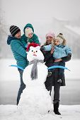 Young family with two sons beside snowman outdoors