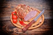 Baked pork neck tomatoes peppers, garlic and knife