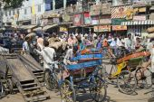 stock photo of rickshaw  - Street crowded with people and cycle rickshaws in Old Delhi - JPG