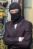 robber in black mask hack server room downloading data on laptop