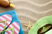 image of suntanning  - Sandy beach background with towel flip flops hat sun glasses suntan oil and starfish - JPG