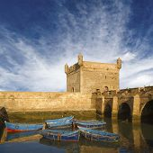 Essaouira port with blue fishing boats and the fortress of Castelo Real of Mogador, Morocco. Unesco