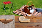 Picnic Table With Wooden Heart, Blanket And Basket In The Grass