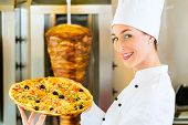 Doner kebab - friendly female vendor in a Turkish fast food eatery, holding a pizza in front of skewer