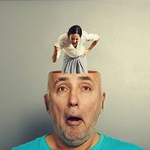angry screaming woman in the head of surprised senior man over grey background