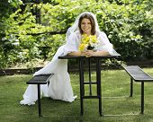 A beautiful young bride laying across a picnic table, the train of her gown drooping across a seat t