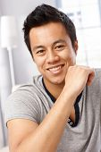 Closeup portrait of handsome young Asian man smiling happy, looking at camera.