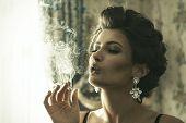 stock photo of smoking woman  - Elegant sexy brunette woman smoking a cigarette - JPG